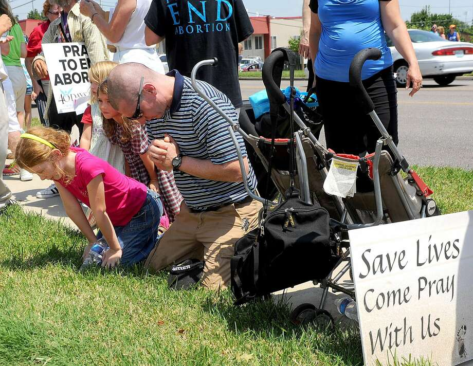 Stephen Smith of Eldon, Mo., prays with his children from left, Gracie, 9, Rachel, 4, and Claire, 6, in front of the Planned Parenthood of Kansas and Mid-Missouri during a rally Tuesday, July 28, 2015, in Columbia, Mo. About forty pro-abortion rights supporters and seventy anti-abortion supporters stood in front of the clinic holding signs as anti-abortion speakers including Mo. Rep. Diane Franklin and Missouri gubernatorial candidate Catherine Hanaway called on state and federal officials to investigate and defund Planned Parenthood.  (Don Shrubshell/Columbia Daily Tribune via AP) Photo: Don Shrubshell, Associated Press