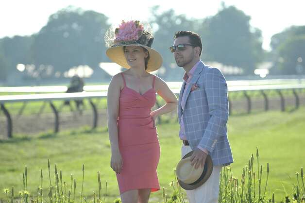Shalyn Barakat, left, wears a hat by Stop Staring. Her dress is custom label for Frivolous. Clothing provided by Frivolous in Saratoga Springs. James Galliher wears Maui Jim sunglasses, an Empire Clothiers blazer, Stone Rose shirt, Jeckerson slacks, Martin Dingman leather belt and Peter Millar loafers. He?s holding a Dobbs hat. Clothing provided by The National in Saratoga Springs. (Photo by Paul Buckowski / Times Union)