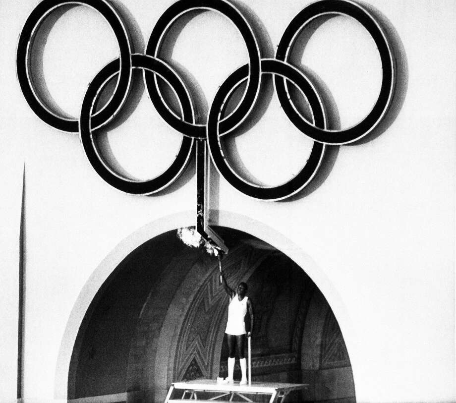 FILE - This July 27, 1984, file photo, shows 1960 Olympic Decathlon Gold Medalist Rafer Johnson lighting the Olympic torch during the Opening Ceremonies of the 23rd Olympiad in Los Angeles. Los Angeles officials are exploring the possibility of launching a joint bid with the Bay Area for the 2024 Games. Photo: Anonymous, Associated Press