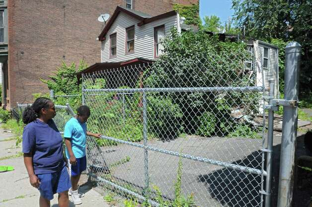 Stephanie DeWitt of Troy and her son Erick Berkely,11, look at a vacant house on King St. partially collapsed Tuesday, July 28, 2015 in Troy, N.Y. It was torn down later Tuesday. (Lori Van Buren / Times Union). (Lori Van Buren / Times Union) Photo: Lori Van Buren