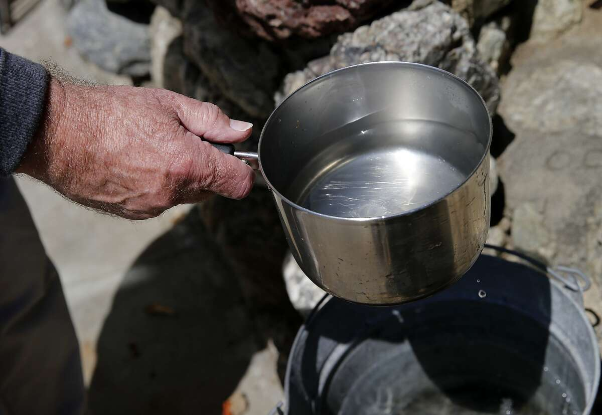 Homeowner William Wood takes a pan of water from a bucket, which gathers water in his kitchen sink, to water some trees in his backyard Tuesday July 28, 2015. Two watering methods are detailed for irrigating trees and shrubs in a neighborhood in San Francisco, Calif.