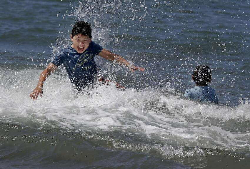 The Riley-Hernandez brothers, who live in the Mission district, played in the surf to cool off Tuesday July 28, 2015. Very warm weather for San Francisco, Calif. brought a crowd out to East Beach in the Presidio.