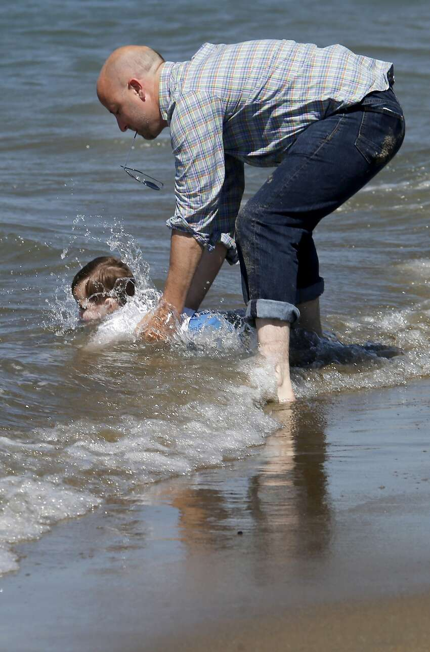 Little Riis Schaeffer met the surf at East Beach full on before his father Jason could come to his rescue Tuesday July 28, 2015. Very warm weather for San Francisco, Calif. brought a crowd out to East Beach in the Presidio.