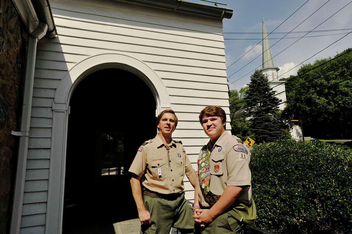 Troop 11 Assistant Scout Master Bill Janocha, and his 16-year-old son Chris, pose for a photograph outside the troop's meeting place across from North Stamford Congregational Church, the troop's sponsor, in Stamford, Conn., on Tuesday, July 28, 2015. Chris is trying for his Eagle Scout rank, his father received his in 1974 and his grandfather achieved his Eagle Scout rank in 1944.
