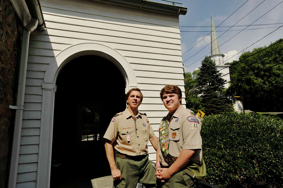 Troop 11 Assistant Scout Master Bill Janocha, and his 16-year-old son Chris, pose for a photograph outside the troop's meeting place across from North Stamford Congregational Church, the troop's sponsor, in Stamford, Conn., on Tuesday, July 28, 2015. Chris is trying for his Eagle Scout rank, his father received his in 1974 and his grandfather achieved his Eagle Scout rank in 1944. Photo: Jason Rearick / Hearst Connecticut Media / Stamford Advocate