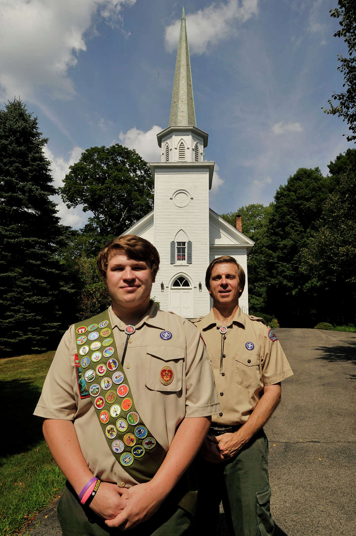 Troop 11 Assistant Scout Master Bill Janocha, and his 16-year-old son Chris, in front of North Stamford Congregational Church, the troop's sponsor. Chris is trying for his Eagle Scout rank; his father received his in 1974; and his grandfather achieved his in 1944.