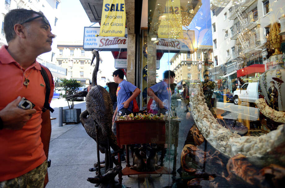 Josep Sensada looks at an item billed as a mammoth tusk in the window of the Ravanelli's gallery in Chinatown. Photo: Brandon Chew / Brandon Chew / The Chronicle / ONLINE_YES