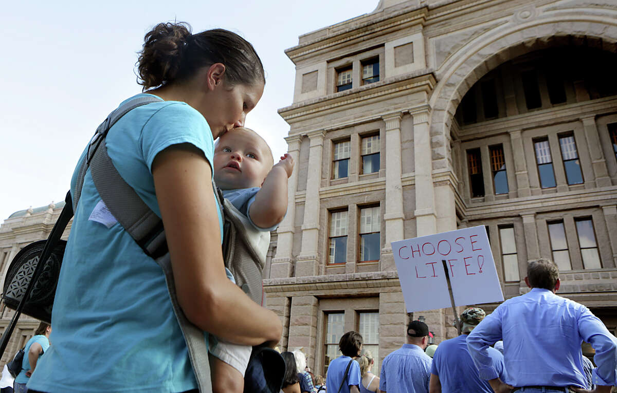 Katharina Peterson of Austin, kisses her 8 month old son, Alexander Peterson as they attend with other supporters of Texas Alliance for Life, an anti-abortion rally at the Texas Capitol on Tuesday, July 28, 2015, in Austin, Texas.