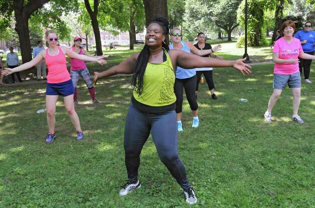 Instructor Cassandra Carter, center, leads a free Zumba class as part of Department of Recreation's 1609 Challenge at Academy Park on Tuesday, July 28, 2015 in Albany, N.Y.  Albany Mayor Kathy Sheehan, right, also participated. (Lori Van Buren / Times Union) Photo: Lori Van Buren / 00032755A