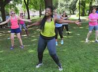 Instructor Cassandra Carter, center, leads a free Zumba class as part of Department of Recreation's 1609 Challenge at Academy Park on Tuesday, July 28, 2015 in Albany, N.Y.  Albany Mayor Kathy Sheehan, right, also participated. (Lori Van Buren / Times Union)