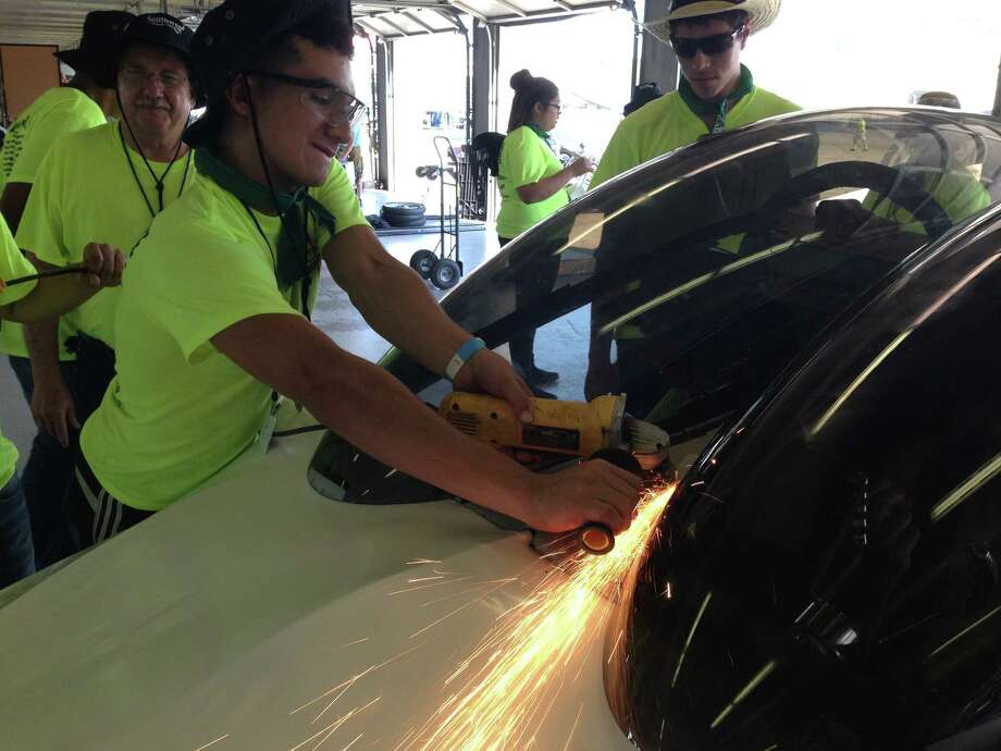 Alan Melecio, 18, makes some final adjustments to the Southwest Engineering Team's solar car during the Solar Car Challenge at the Texas Motor Speedway on July 20. Photo: Courtesy Southwest ISD