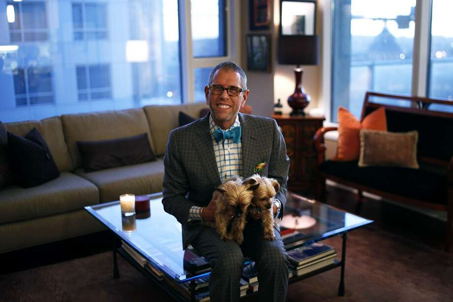 "Andrew Freeman sits with his Yorkie dogs, Daisy and Tulip, within his condo on the 22nd floor of the Soma Grand.  Freeman is the owner of Andrew Freeman & Co., a restaurant and hospitality consulting business in San Francisco.  He will be appearing on an upcoming episode of ""Million Dollar Listing San Francisco."" Photo: Cameron Robert, The Chronicle"