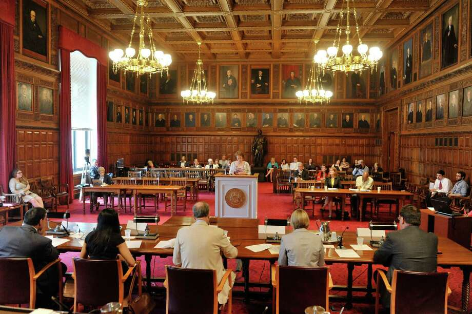 Denise Kronstadt, background at podium, deputy executive director/ director of advocacy for The Fund for Modern Courts, testifies during a public hearing of the  Commission on Statewide Attorney Discipline, held at the New York State Court of Appeals on Tuesday, July 28, 2015, in Albany, N.Y.   (Paul Buckowski / Times Union) Photo: PAUL BUCKOWSKI / 00032796A