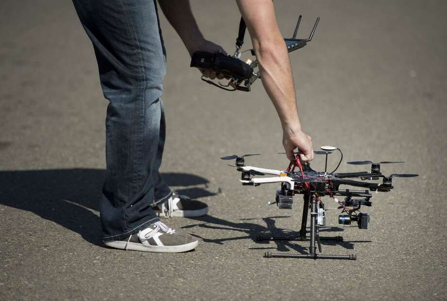 Christopher Brown, co-owner of Next New Homes Group, reaches for his multi-rotor helicopter drone after taking aerial video of a home in Sacramento, Calif., in February. Photo: Randy Pench /McClatchy-Tribune News Service / Sacramento Bee