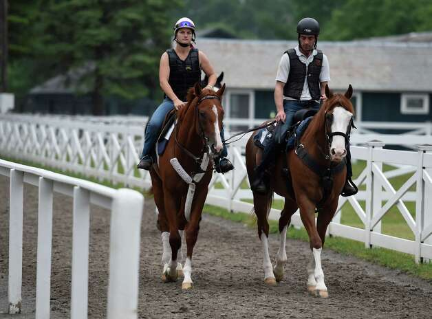 Belmont Stakes hopeful Frammento with exercise rider Heather Stark aboard, left,  goes out for a long gallop on the Oklahoma Training Center track Thursday morning May 28, 2015 in Saratoga Springs, N.Y.  (Skip Dickstein/Times Union) Photo: SKIP DICKSTEIN / 00032045A