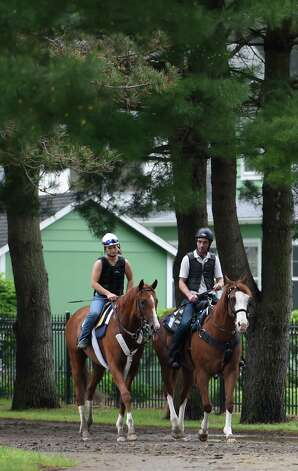 Belmont Stakes hopeful Frammento with exercise rider Heather Stark aboard, left,  goes returns from a long gallop on the Oklahoma Training Center track Thursday morning May 28, 2015 in Saratoga Springs, N.Y.  (Skip Dickstein/Times Union) Photo: SKIP DICKSTEIN / 00032045A