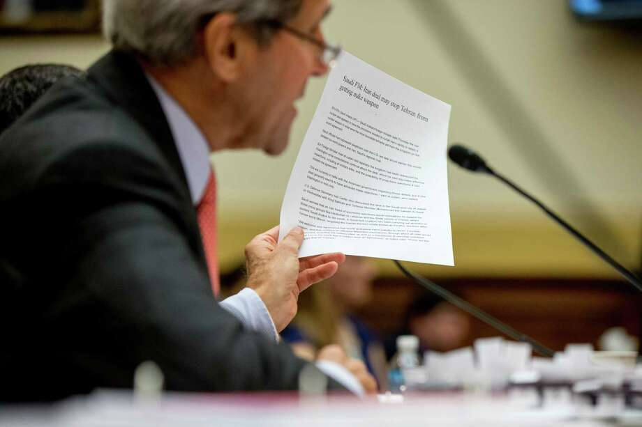 Secretary of State John Kerry holds up an article as he testifies on Capitol Hill in Washington, Tuesday, July 28, 2015, before the House Foreign Affairs Committee hearing on the Iran Nuclear Agreement. Kerry pitched the administration's controversial nuclear deal with Iran before a skeptical House Foreign Affairs Committee on Tuesday, pushing back against the allegation it would ease crippling sanctions forever in exchange for temporary concessions on weapons development. (AP Photo/Andrew Harnik) ORG XMIT: DCAH135 Photo: Andrew Harnik / AP