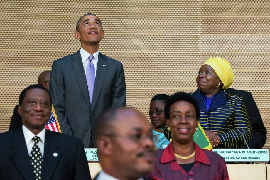 African Union Commission chairperson, Dr. Nkosazana Dlamini-Zuma, right, stands with U.S. President Barack Obama as he looks up at the crowd before delivering a speech to the African Union, Tuesday, July 28, 2015, in Addis Ababa, Ethiopia. On the final day of his African trip, Obama is focusing on economic opportunities and African security. (AP Photo/Evan Vucci) ORG XMIT: ETEV114 Photo: Evan Vucci / AP