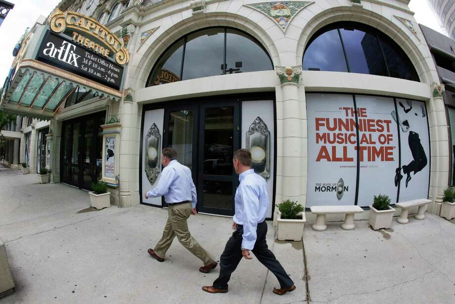 People walk past signs announcing the Book of Mormon musical at the Capitol Theatre, Monday, July 27, 2015, in Salt Lake City. The biting satirical musical that mocks Mormons is finally coming to the heart of Mormonlandia, starting a sold-out, two week run on Tuesday, July 28, 2015, at a theater two blocks from the church's flagship temple and headquarters. (AP Photo/Rick Bowmer) ORG XMIT: UTRB301 Photo: Rick Bowmer / AP