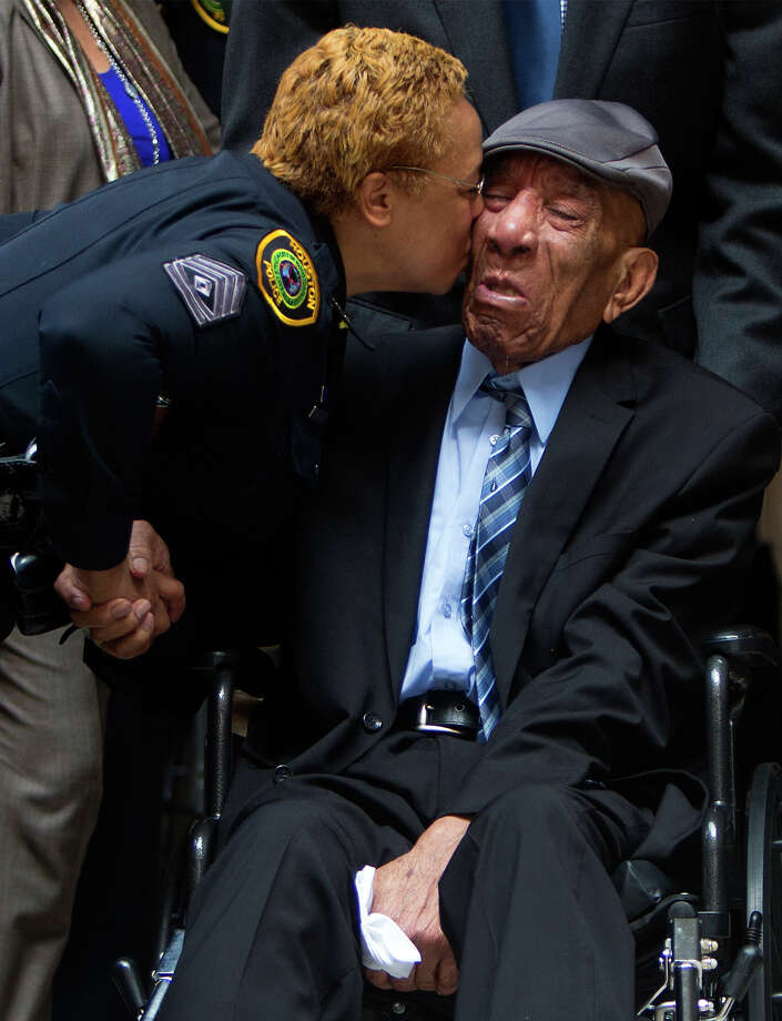"Sgt. G. Captain kisses Edward A. Thomas on the cheek before a ceremony naming the Houston Police Department Headquarters after him, Monday, July 27, 2015, in Houston. Captain has known Thomas for 25 years. ""He's been through so much you just wouldn't believe,"" she said. The building was named in his honor after his 63 years of exemplary service and dedication to the department. (Cody Duty/Houston Chronicle via AP) Photo: Cody Duty, Associated Press / Houston Chronicle"