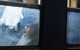 TOPSHOTS A migrant woman sits in a coach at a train headed to Serbia in the town of Gevgelija on July 27, 2015, on the Macedonian-Greek border. The migrants, among them children and elderly people are trying to cross Macedonia and Serbia and enter the EU via Hungary. Hungarian authorities started building a fence along the country's border with Serbia earlier this week to halt the migrant influx. AFP PHOTO/ROBERT ATANASOVSKIROBERT ATANASOVSKI/AFP/Getty Images