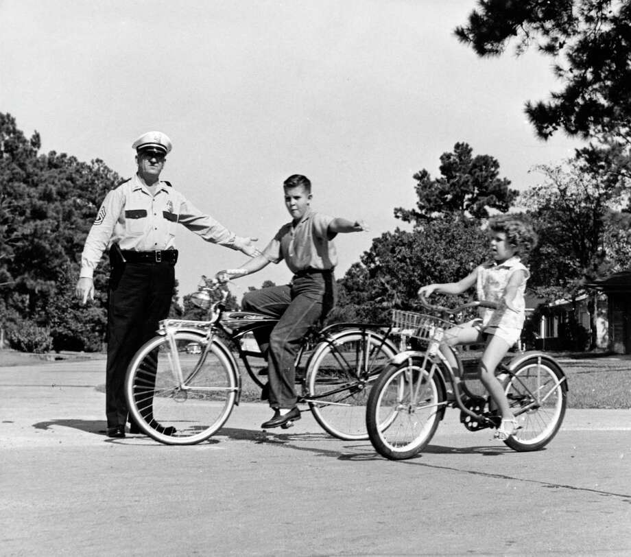A Houston police officer teaches bicycle safety to two local youths, Sept., 1959. Photo: Tom Colburn, © Houston Chronicle / Houston Chronicle
