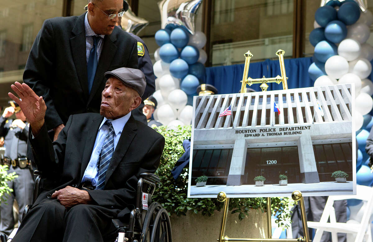 Edward A. Thomas waves as he sits near a photo showing how the Houston Police Headquarters will look when the building is named after him, Monday, July 27, 2015, in Houston. The building was named in his honor after his 63 years of exemplary service and dedication to the department.