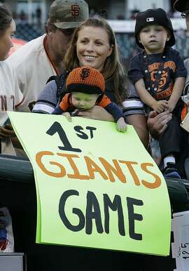 Terra Beaudin, center, holds her 2-month old child Beckam before a baseball game between the San Francisco Giants and the Milwaukee Brewers in San Francisco, Monday, July 27, 2015. (AP Photo/Jeff Chiu)
