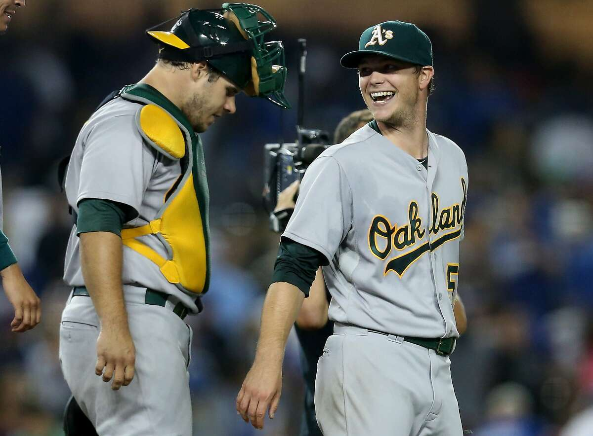 LOS ANGELES, CA - JULY 28: Starting pitcher Sonny Gray #54 (R) and catcher Josh Phegley #19 of the Oakland Athletics celebrate after Gray's complete game shutout victory over the Los Angeles Dodgers at Dodger Stadium on July 28, 2015 in Los Angeles, California. The Athletics won 2-0. (Photo by Stephen Dunn/Getty Images)