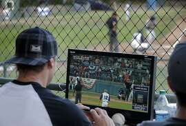 Eric Byrnes watches the screen which displays the pitch calls before he announces them as the San Rafael Pacifics became the first professional baseball team to have balls and strikes determined by a computer, during their game against the Vallejo Admirals at Albert Park in San Rafael, Calif., on Tuesday, July 28, 2015. The called strikes and balls were announced by Eric Byrnes to benefit the Pat Tillman Foundation.