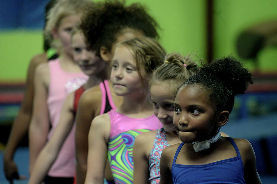 Six-year-old Autumn Boswell and teammates line up for their next drill at Olympic Dreams in Lumberton Tuesday. Despite having a trach tube, Autumn is determined to excel in the world of gymnastics.  Photo taken Tuesday, July 28, 2015  Kim Brent/The Enterprise Photo: Kim Brent / Beaumont Enterprise