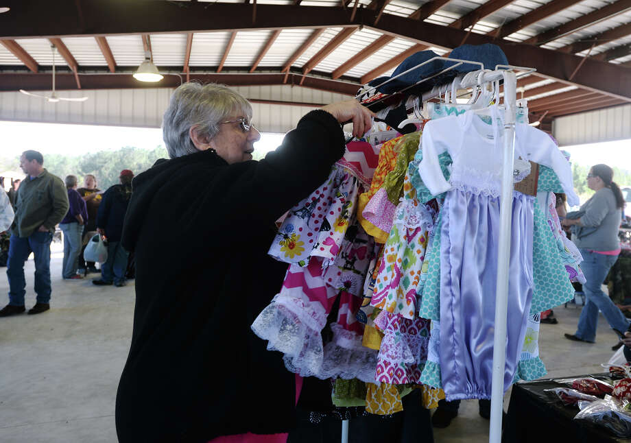 Cecilia Shirley, owner of Grandma's Closet, tends to a rack of clothing at her both at the Frank K. Rudisaile Pavilion on Saturday. Several hundred people came to downtown Silsbee's pavilion for the Hardin County Texas Auction Trunk Sale on Saturday morning. Organizers said the event drew between 30 and 40 vendors, not including downtown merchants who moved some of their wares to the sidewalks.  Photo taken Saturday 2/7/15  Jake Daniels/The Enterprise Photo: Jake Daniels / ©2014 The Beaumont Enterprise/Jake Daniels