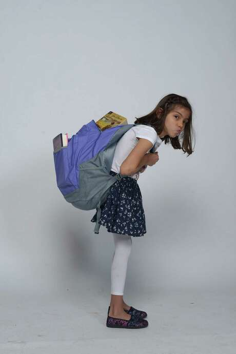 A too-large backpack can easily be overstuffed with books and other items, making it dangerously heavy. As a rule of thumb, a fully loaded pack should weigh no more than 10 percent to 15 percent of the child's weight. That means a maximum of 7.5 pounds for a 50-pound child and 15 pounds for a 100-pound child. Photo: Billy Calzada /San Antonio Express-News / San Antonio Express-News