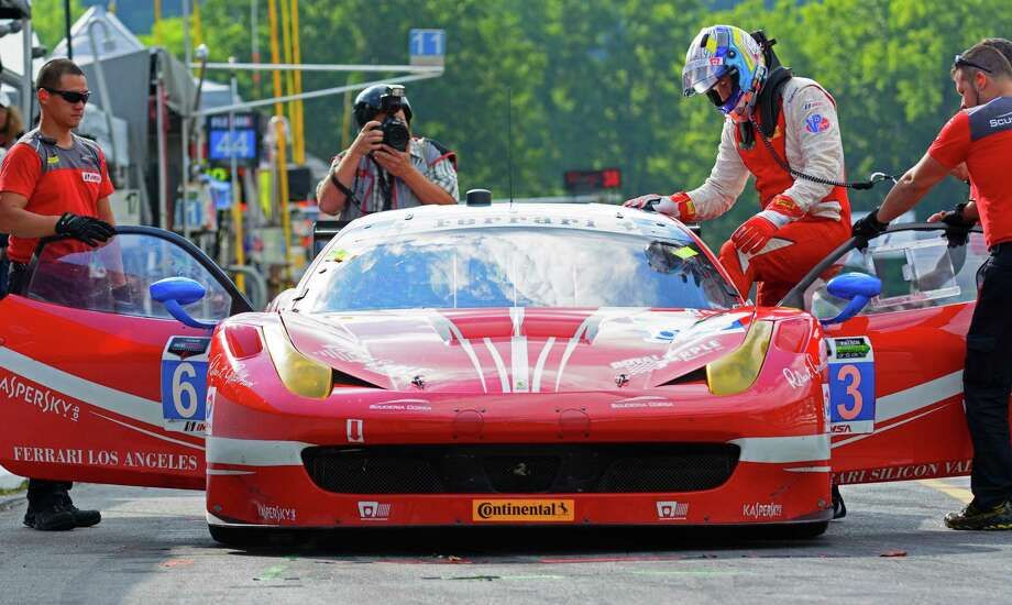 Westporter Bill Sweedler, left, climbs into his Ferrari 458 Italia prior to a TUDOR series race at Lime Rock Park in Lakeville, Connecticut on Saturday, July 25, 2015. Photo: Bob Chapman/Contributed Photo / Westport News Contributed