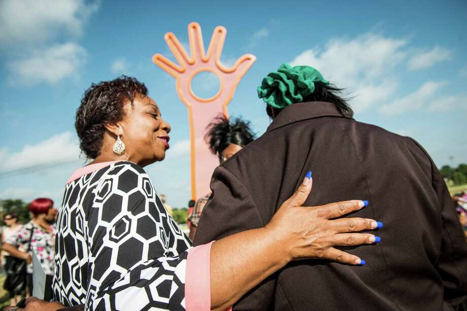 """Cynthia Hornsby, former executive director of the Davis-Scott YMCA and current volunteer, left, talks to Beverly Watts of the San Antonio Housing Authority, right, at the dedication of the new """"Open Hand, Open Mind, Open Heart,"""" art piece at Pittman-Sullivan Park in the East side neighborhood in San Antonio on Wednesday, July 29, 2015. The project is a collaboration between City Council District 2, the Department for CUlture and Creative Development's Public Art San Antonio, Transportation and Capital Improvements, Parks and Recreation, and the Davis-Scott Family YMCA. The committee commissioned Boston artist Douglas Kornfeld to create the 32-foot tall sculpture consisting of perforated steel and metal tubing, opening up the neighborhood to the city of San Antonio. Photo: Matthew Busch, For San Antonio Express-News / For San Antonio Express-News / © Matthew Busch"""