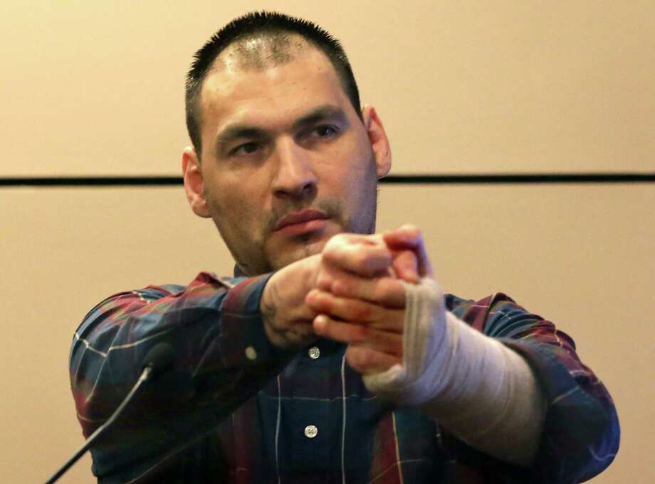 Jose Gonzalez, found guilty Thursday in the murder of his roommate Ahn Cisneros, shows the jury how he held the gun as he shot Cisneros, during testimony in the 144th State District Court in the Cadena-Reeves Justice Center on Wednesday, July 29, 2015. Photo: Bob Owen /San Antonio Express-News / ©2015 San Antonio Express-News
