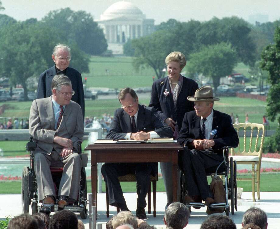 President George H.W. Bush signs the Americans with Disabilities Act during a ceremony on the South Lawn of the White House in 1990. Joining the president are Evan Kemp (left), chairman of the Equal Opportunity Employment Commission; the Rev. Harold Wilke; Sandra Parrino, chairman of the National Council on Disability; and Justin Dart, chairman of the President's Council on Disabilities. Photo: Barry Thumma, Associated Press
