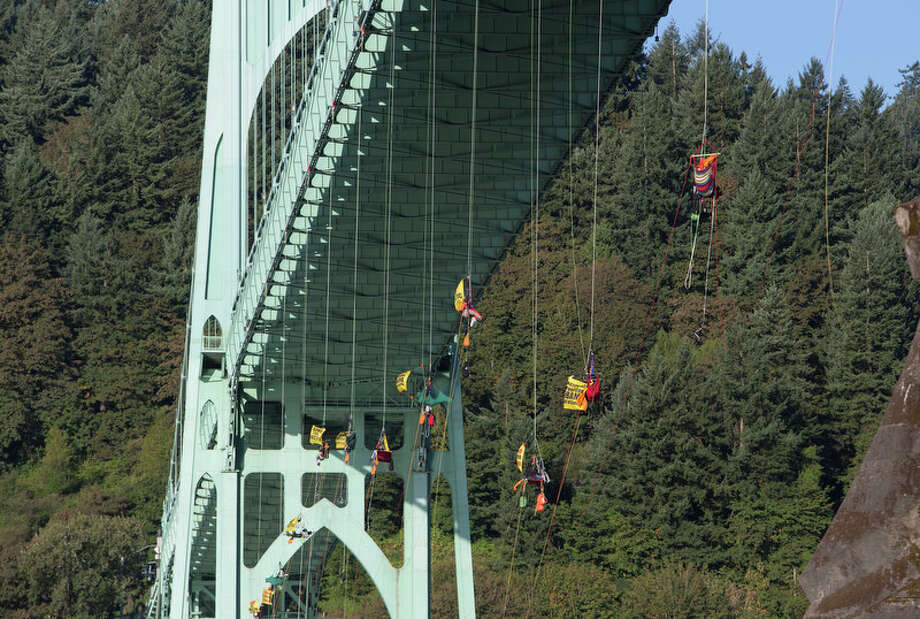 Activists hang under the St. Johns Bridge in Portland, Ore., in an attempt to block the Shell leased icebreaker, MSV Fennica Wednesday. The climbers are currently preventing the ship from passing underneath the bridge on its way to meet Shell's drilling fleet. The climbers have enough supplies to last for several days. According to the latest federal permit, the Fennica must be at Shell's drill site before Shell can reapply for federal approval to drill deep enough for oil in the Chukchi Sea. Photo: Craig Mitchelldyer
