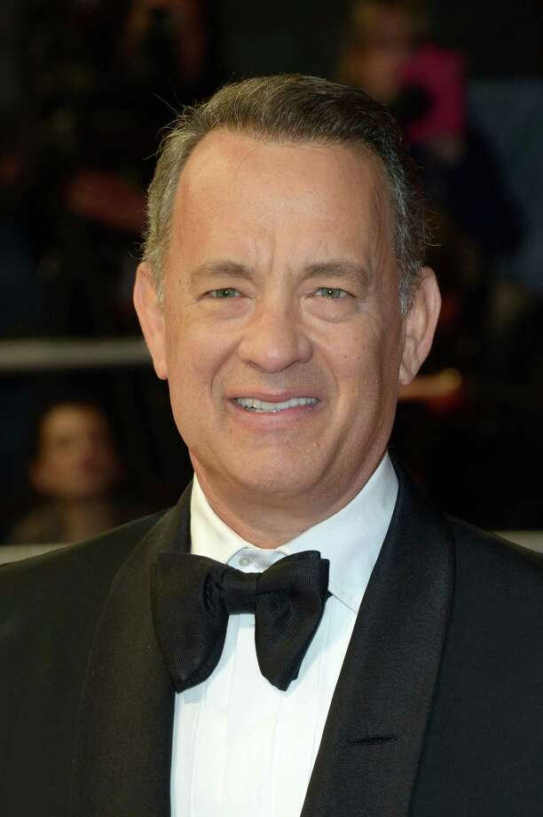 """FILE - In this Feb. 16, 2014 file photo, actor Tom Hanks poses for photographers on the red carpet at the EE British Academy Film Awards held at the Royal Opera House in London. Hanks started shooting portions of his new film """"A Hologram for the King"""" in Egypt's Red Sea resort city of Hurghada, the country's state news agency reported Saturday, July 19, 2014. (photos by Jon Furniss/Invision/AP, File) ORG XMIT: NY119 Photo: Jon Furniss / Invision"""