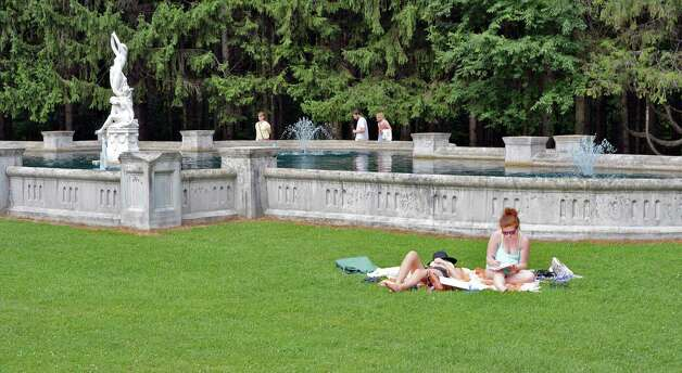 Skidmore students Michaela Kerxhalli, left, of Upton, Mass., and Emma McCully of Wilton, Conn., get some sun on the grounds of Yaddo Saturday July 25, 2015 in Saratoga Springs, NY.  (John Carl D'Annibale / Times Union) Photo: John Carl D'Annibale / 00032751A
