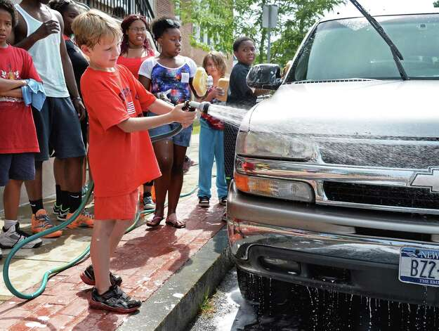 Eight-year-old Mason Mcguire, with hose, learns about business while keeping cool during the 21C Summer Program's car wash and lemonade stand fund raiser at Van Corlaer Elementary School Wednesday July 29, 2015 in Schenctady, NY. The program teaches students how to run a business. (John Carl D'Annibale / Times Union) Photo: John Carl D'Annibale / 10032813A