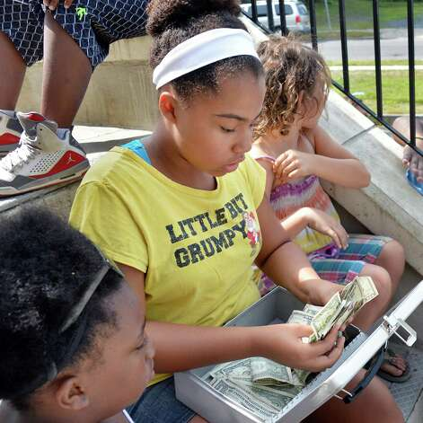 Ten-year-old Jannise Jackson, center, counts the proceeds from a car wash and lemonade stand run by students at the 21C Summer Program at Van Corlaer Elementary School Wednesday July 29, 2015 in Schenctady, NY. The program teaches students how to run a business. (John Carl D'Annibale / Times Union) Photo: John Carl D'Annibale / 10032813A