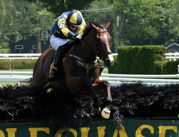 Overwhelming ridden by jockey Sean McDermott glides over the last fence of a two and one sixteenth mile steeplechase even on the inner turf track at the Saratoga Race course this afternoon July 29, 2015 in Saratoga Springs, N.Y.    (Skip Dickstein/Times Union) Photo: SKIP DICKSTEIN