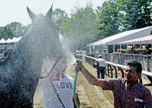 American Passage is given a cooling spray of water by his trainer Rudy Rodriguez after the second race at the Saratoga Race course this afternoon July 29, 2015 in Saratoga Springs, N.Y.    (Skip Dickstein/Times Union) Photo: SKIP DICKSTEIN