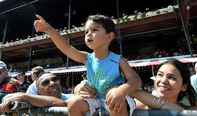 Three year old Avory Cordero, center focuses on the horses as his grandfather and Racing Hall of Fame member Angel Cordero Jr., left,  and his mother Canela Cordero, right watch his fascination at the Saratoga Race course this afternoon July 29, 2015 in Saratoga Springs, N.Y.    (Skip Dickstein/Times Union) Photo: SKIP DICKSTEIN