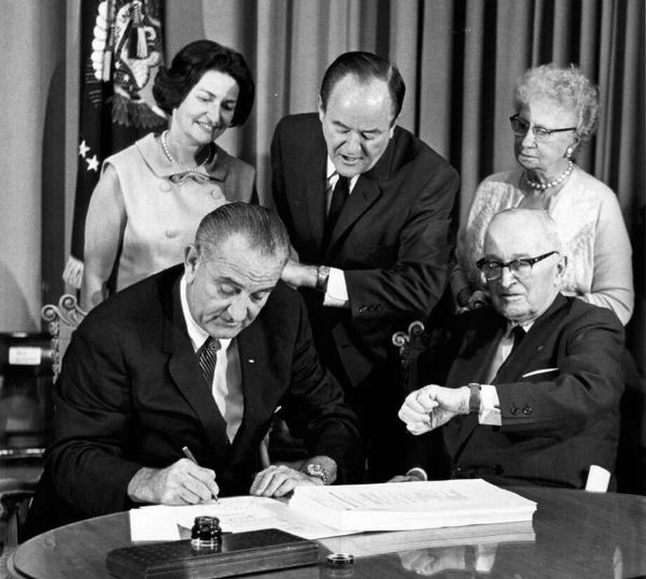 On July 30, 1965, President Lyndon Johnson signs the Medicare Bill (which created both Medicare and Medicaid) while former President Harry S. Truman, right, observes. At rear are Lady Bird Johnson, Vice President Hubert Humphrey, and former first lady Bess Truman. Photo: File, AP