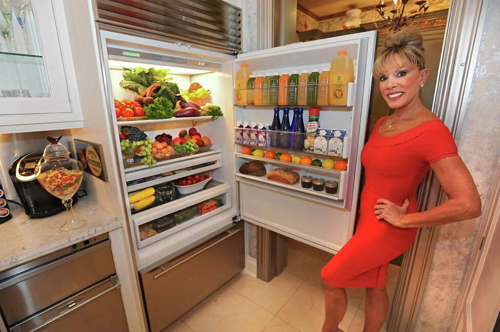 Michele Riggi stands next to her fridge in her kitchen on Thursday, July 23, 2015 in Saratoga Springs, N.Y.
