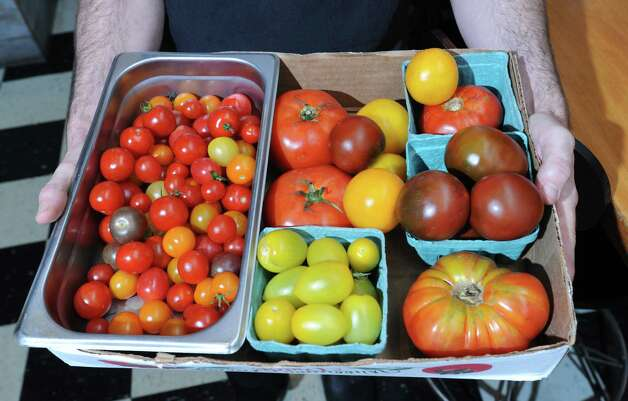 Chef Rory Moran holds some heirloom tomatoes he procured at a farmers market inside Comfort Kitchen on Thursday, July 23, 2015 in Saratoga Springs, N.Y. (Lori Van Buren / Times Union) Photo: Lori Van Buren / 00032706A