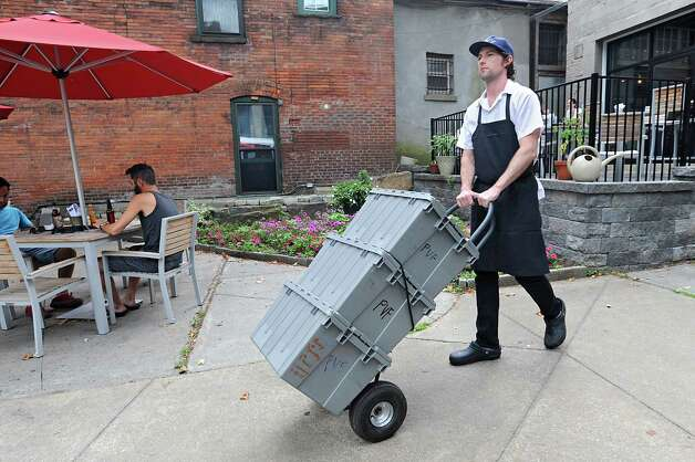 Chef Rory Moran pushes his handcart outside Comfort Kitchen on Thursday, July 23, 2015 in Saratoga Springs, N.Y. He uses the hand cart to procure ingredients for the restaurant.  (Lori Van Buren / Times Union) Photo: Lori Van Buren / 00032706A