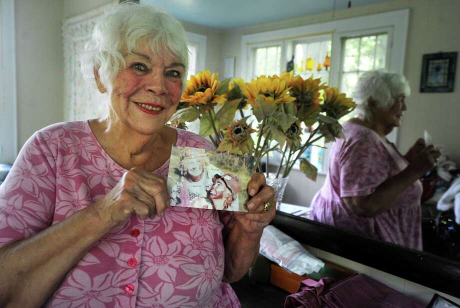 Jeanne Harrison holds a photo from her time training as a clown under the tutelage of Wavy Gravy on Tuesday at her home in Fairfield. Once again, Wavy Gravy is the host of the Gathering of the Vibes music festival in Bridgeport. Photo: Autumn Driscoll / Hearst Connecticut Media / Connecticut Post